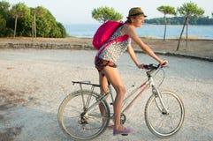 Flicka som cyklar vid havet Arkivfoton