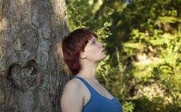 Flicka som dagdrömmer om förälskelse i skog arkivbild