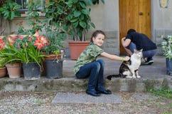 Flicka som daltar en katt Arkivbild