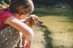 Flicka som daltar hennes hund arkivbild