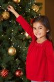 Flicka som dekorerar julgranen Royaltyfria Bilder