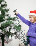 Flicka som dekorerar julgranen med felika ljus Royaltyfri Foto