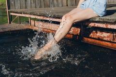 Flicka som doppar fot i vattnet och skratta Fotografering för Bildbyråer