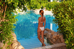 Flicka som downstairs går till simbassängen royaltyfri foto