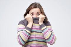 Flicka som drar hennes moderiktiga tröja som har uppe i luften gyckel som är barnsligt försvinna i hennes kläder fotografering för bildbyråer