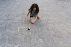 Flicka som drar hoppa hage med krita p? lekplats royaltyfri bild