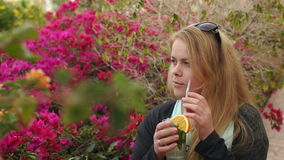Flicka som dricker coctailen från sugröret i parkera stock video