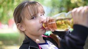 Flicka som dricker en drink från en plast- flaska på en sommardag lager videofilmer