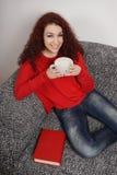 Flicka som dricker en stor kopp kaffe arkivbild