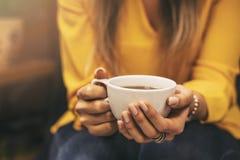 Flicka som dricker en varmt drink och solsken royaltyfri bild