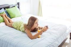 Flicka som dricker fruktsaft och håller ögonen på tv i sovrum Royaltyfria Foton