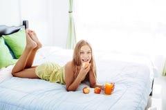 Flicka som dricker fruktsaft och kopplar av i sovrum royaltyfria bilder