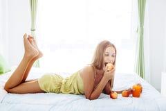 Flicka som dricker fruktsaft och kopplar av i sovrum fotografering för bildbyråer