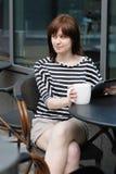 Flicka som dricker kaffe i ett utomhus- kafé Royaltyfri Foto