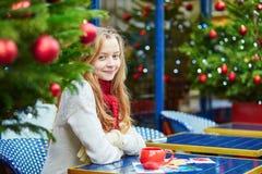 Flicka som dricker kaffe och skriver julvykort Royaltyfri Fotografi