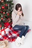Flicka som dricker kaffe under teet för nytt år för julgran Royaltyfria Foton