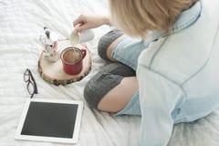 Flicka som dricker morgonkaffe på en läs- minnestavla för vit säng i höga strumpor Arkivbilder