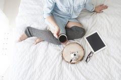 Flicka som dricker morgonkaffe på en läs- minnestavla för vit säng i höga strumpor Arkivbild