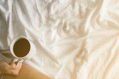 Flicka som dricker morgonkaffe på en läs- minnestavla för vit säng i högt tona för gult ljus för bästa sikt för strumpakopierings Royaltyfri Bild