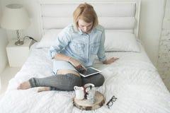 Flicka som dricker morgonkaffe på en vit säng som arbetar på minnestavlan i höga strumpor Arkivbild