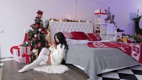 Flicka som dricker te på golv nära julgranen stock video