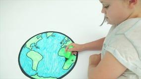 Flicka som färgar i en översikt av världen arkivfilmer