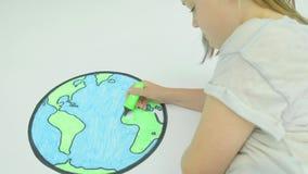 Flicka som färgar i en översikt av världen stock video
