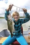 Flicka som fångar stora Bass In Boat On Lake Arkivbild