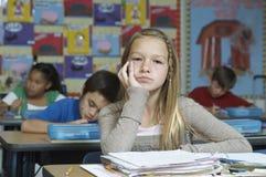 Flicka som får borrad medan klasskompisar som skriver anmärkningar i bakgrunden Arkivbilder