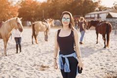Flicka som förbereder sig att rida en häst arkivfoto