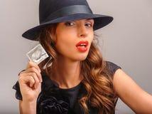 Flicka som föreslår en kondom Royaltyfri Foto
