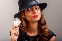 Flicka som föreslår en kondom Arkivfoto