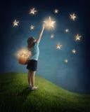 Flicka som försöker att fånga en stjärna Arkivbild