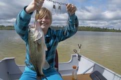 Flicka som fångar stora Bass In Boat On Lake Arkivfoton