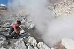 Flicka som fotograferar ånga fumarolen på den aktiva vulkan för krater Arkivfoto