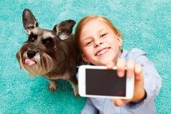 Flicka som fotograferar sig och hennes hund Arkivfoto