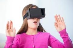 Flicka som får erfarenhet genom att använda VR-hörlurar med mikrofon exponeringsglas Royaltyfri Foto