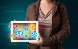 Flicka som framlägger en tablet med färgrika sociala symboler och tecken Arkivfoton