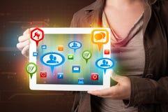 Flicka som framlägger en tablet med färgrika sociala symboler och tecken Royaltyfri Foto