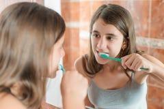 Flicka som framme borstar hennes tänder av en spegel Arkivbilder