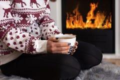 Flicka som framme dricker varmt te av spisen och hemma sitter på päls- matta royaltyfria foton