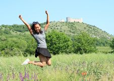Flicka som framme hoppar av slotten Devicky på Palava royaltyfri fotografi