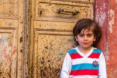 Flicka som framme poserar av en gammal dörr Arkivbild