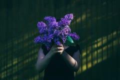 Flicka som framme rymmer den lila buketten av framsidan fotografering för bildbyråer