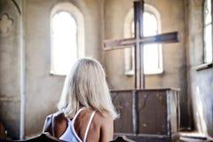 Flicka som framme sitter av korset. royaltyfri fotografi