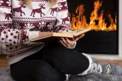 Flicka som framme sitter av spisen och läseboken i lång vinternatt hemma royaltyfria foton