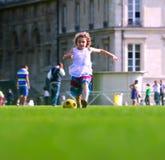 Flicka som framme spelar fotboll skolabyggnaden Arkivfoton