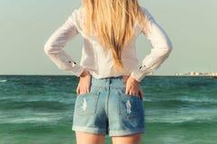 Flicka som framme står av havet Arkivbild