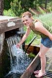 Flicka som fyller på en bevattnatillbringare royaltyfri foto