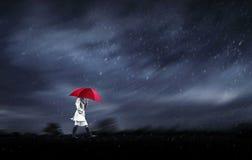 flicka som går i en regnig dag Arkivbild